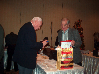 Bob Davis and Hap Williams look over the silent auction items